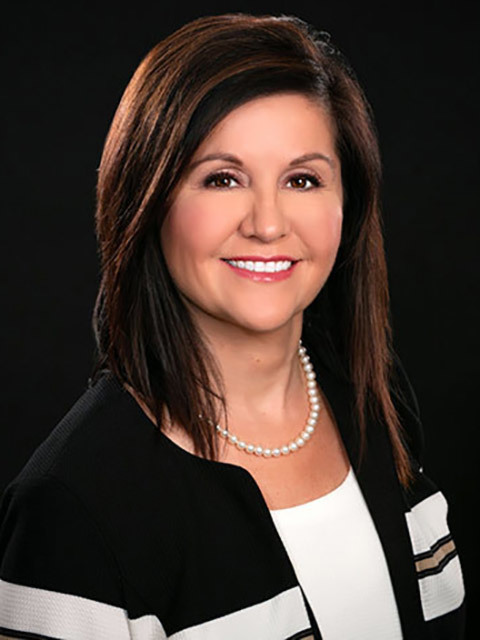 Stevie Craig Executive Director - woman with dark hair in black and white sweater